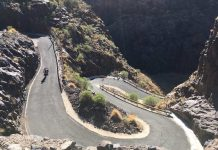 bikerumor pic of the day cyclist is riding a bike with a child trailer carrier down a curvy and windy road in gran canaria spain it is very sunny and the sides of the road are rocky.