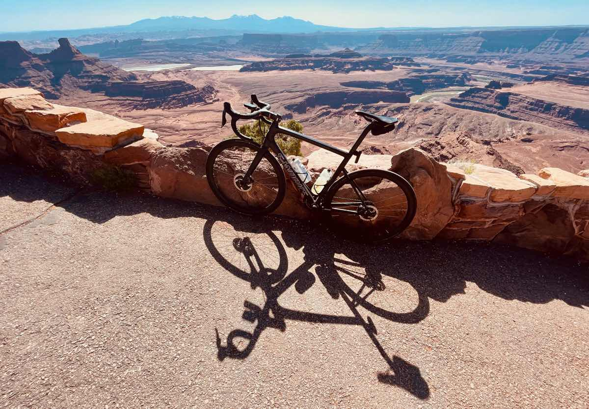 a bicycle at the top of a ridge in moab utah looking out over a red rock valley