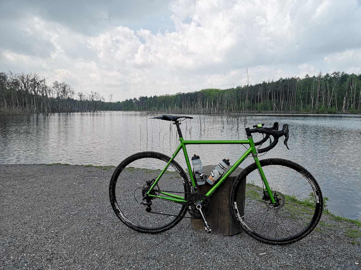 bikerumor pic of the day a green grave bike is on a gravel beach on the edge of a body of water with cloudy sky reflecting in it