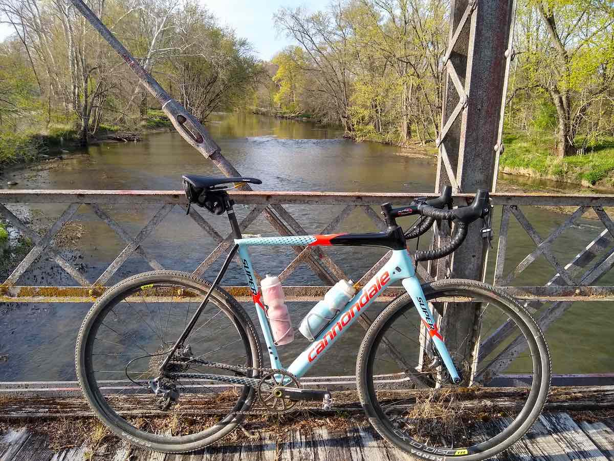 bikerumor pic of the day a carbondale gravel bike sits across a metal bridge over the eel river in indiana the trees and grass along the river banks are just beginning to green out for spring, the day is bright and sunny.