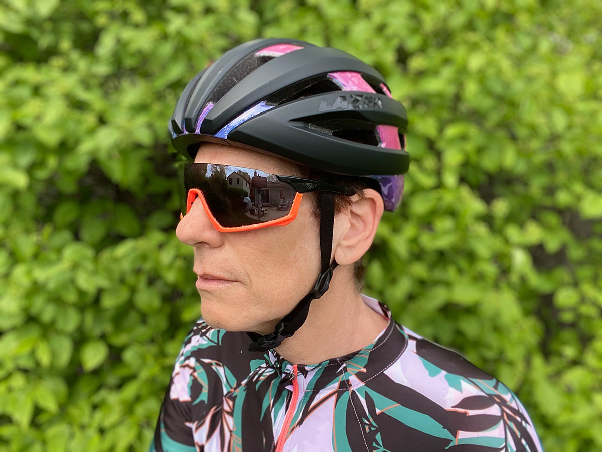 female cyclist showing how a bicycle helmet should fit properly and how the straps should be positioned on the side and under the chin
