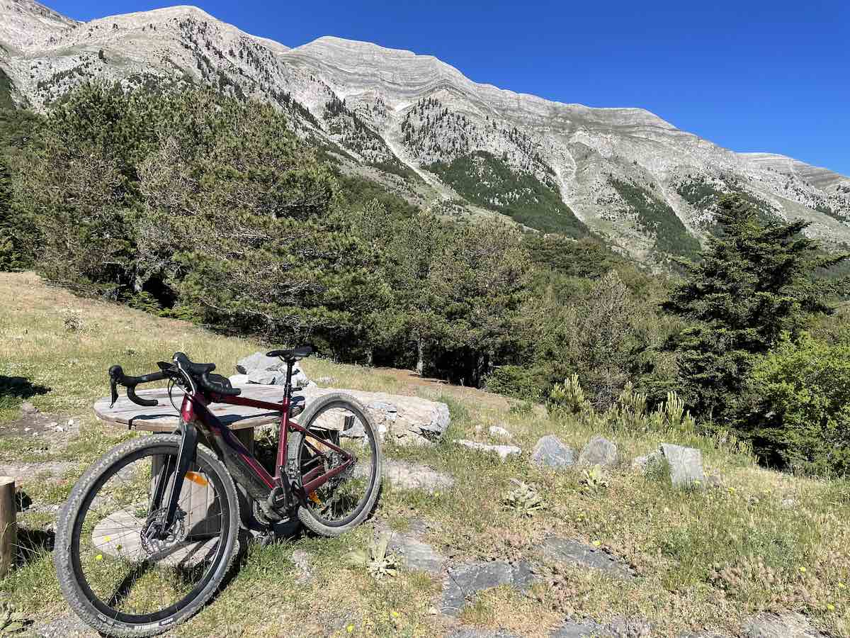 bikerumor pic of the day a gravel bike is perched on the side of Mount Taygetos among the grass and rock outcropping with pine trees and the mountain in the background, the sky is clear blue and it is very sunny