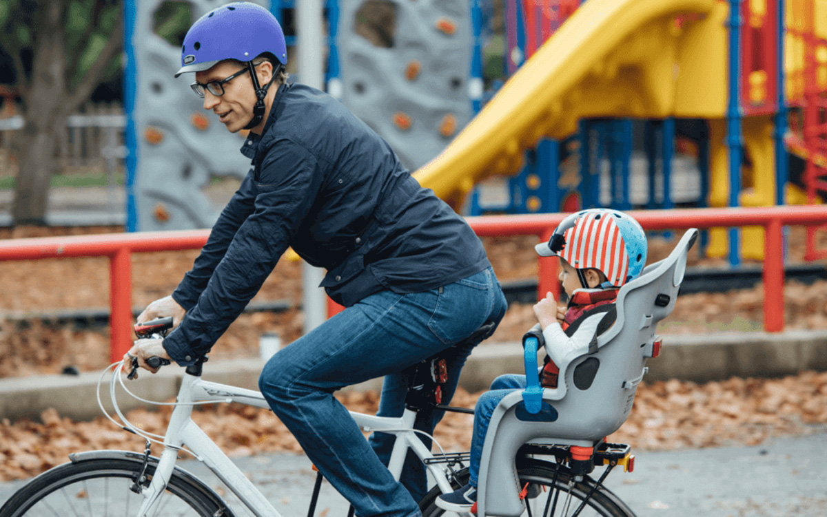 Father and child on bike wearing nutcase helmets