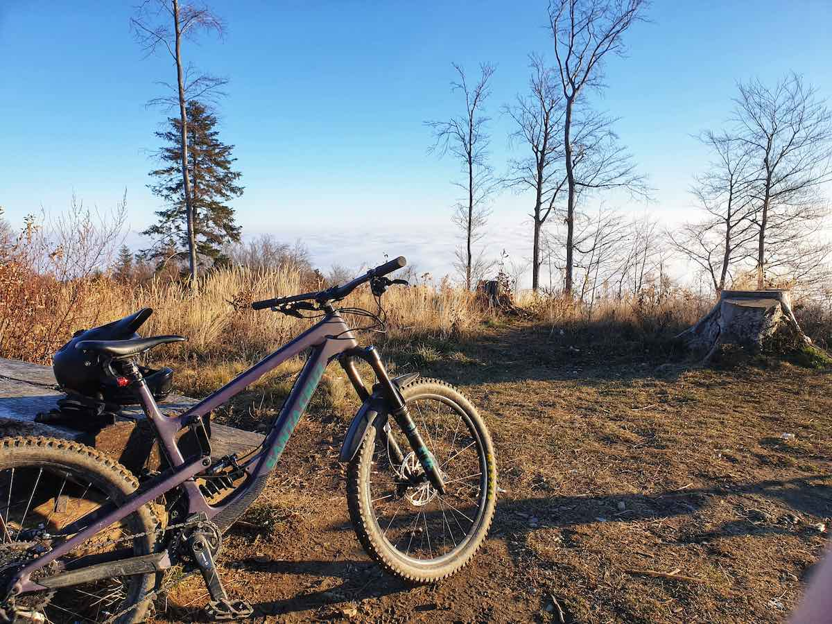 bikerumor pic of the day a mountain bike leans against some logs at the top of sljeme mountain the sun is low and golden on the packed dirt and brush the view is of the clouds over the city of zagreb croatia.