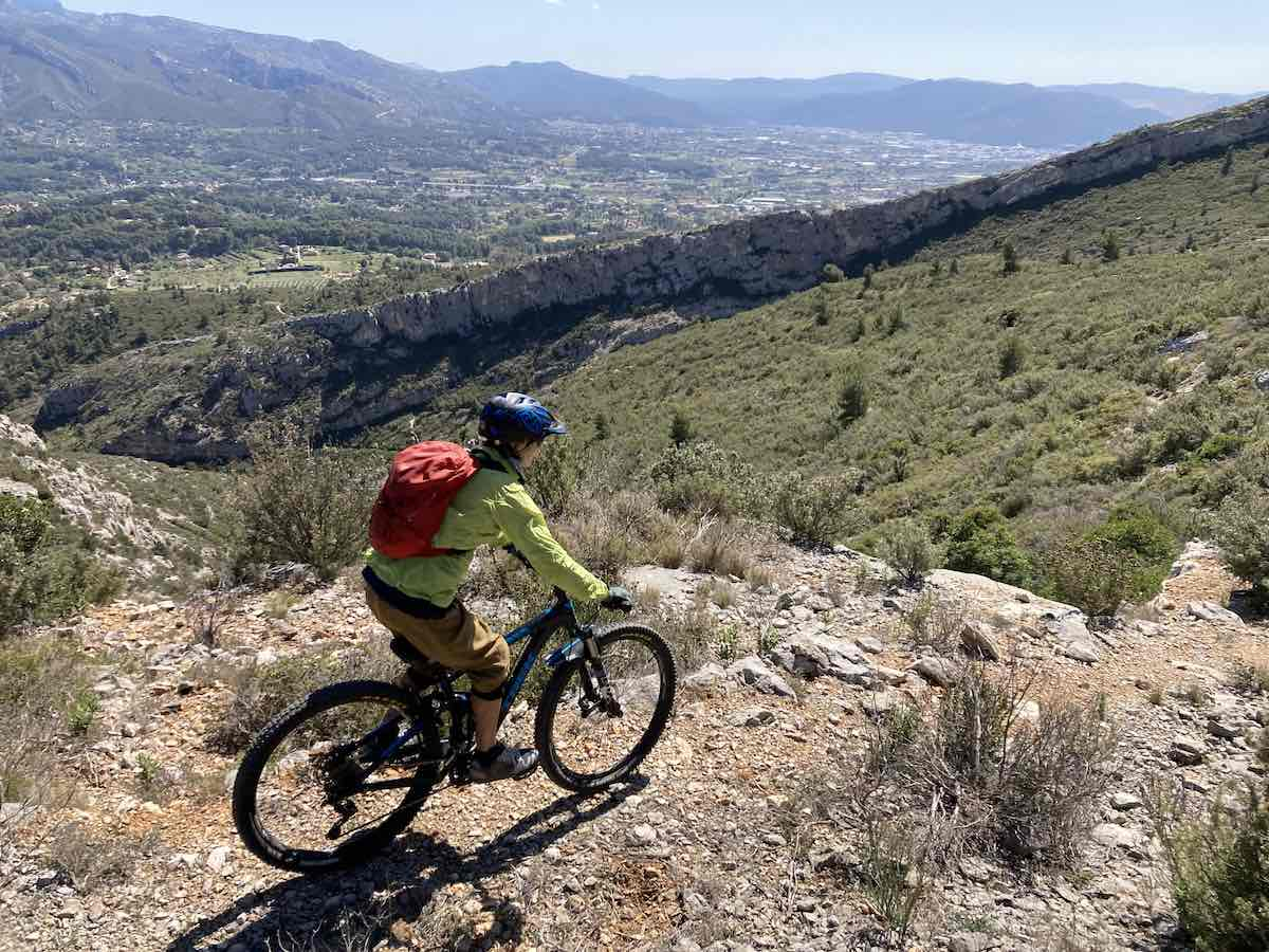 bikerumor pic of the day a mountain biker is on the edge of a trail overlooking rocky outcroppings on the mountain and a valley below, the sun is high and the sky is clear.