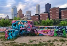bikerumor pic of the day a bicycle is in front of some very colorful graffiti with the skyline of pittsburgh pa in the background the sky is cloudy with bits of blue and light from the sun peeking through.