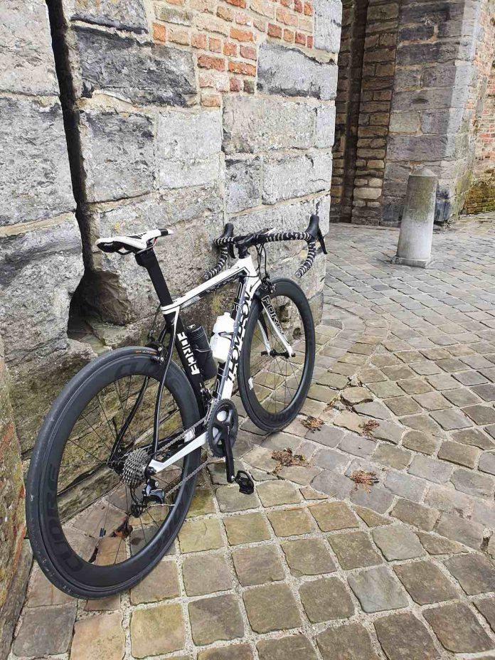 bikerumor pic of the day a bicycle leans against a stone wall and is surrounded by cobble stones in brugge, belgium.