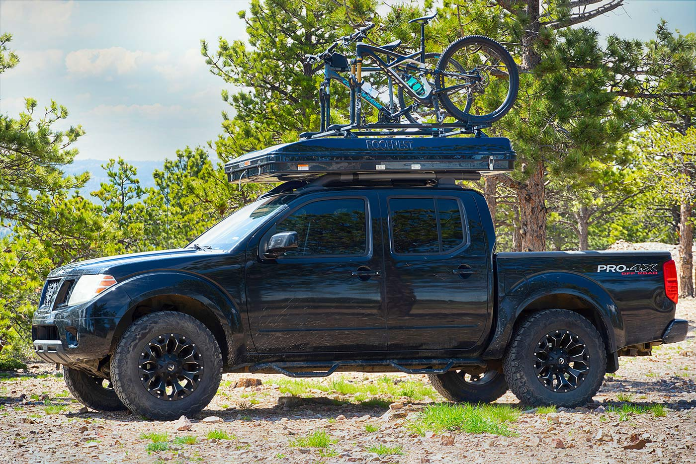roofnest sparrow adventure rooftop tent with bike trays on a pickup truck