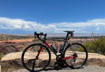 bikerumor pic of the day a bike is atop a mesa overlooking colorado national monument there is red dirt, rocks and low scrub trees the sun is high in the sky and it is bright blue with white clouds in the distance