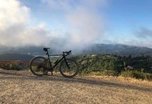 bikerumor pic of the day a bicycle is atop a clearing with clouds and mountaintops in the distance.