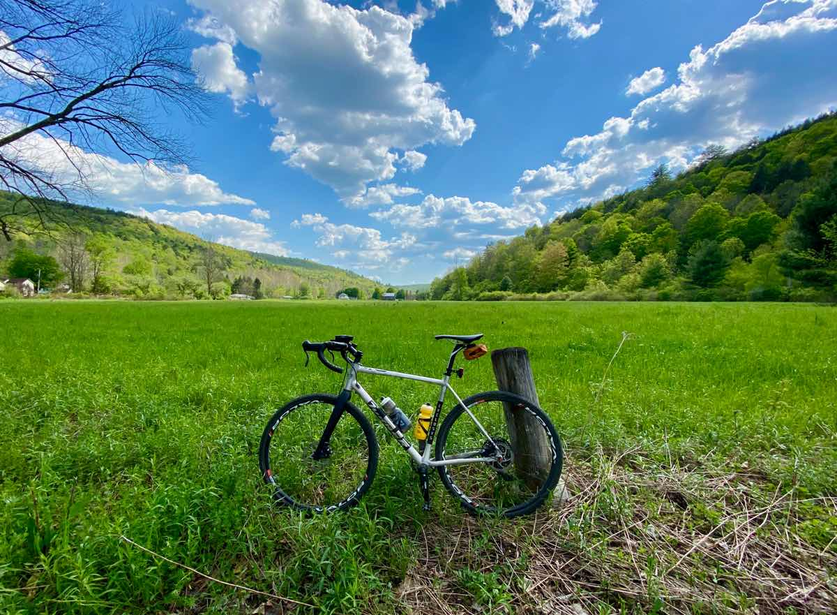 bikerumor pic of the day a bicycle leans against a short wood post in a bright green grassy field surrounded by mountains with bright blue sky filled with fluffy clouds