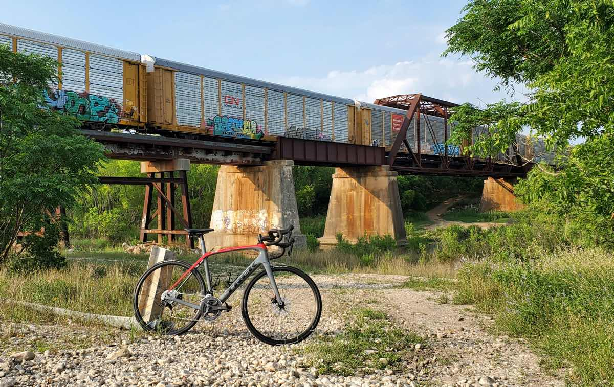 bikerumor pic of the day a bicycle is on a gravel path near a train bridge, there is colorful graffiti on the train cars and scrubby trees on either side of the path.