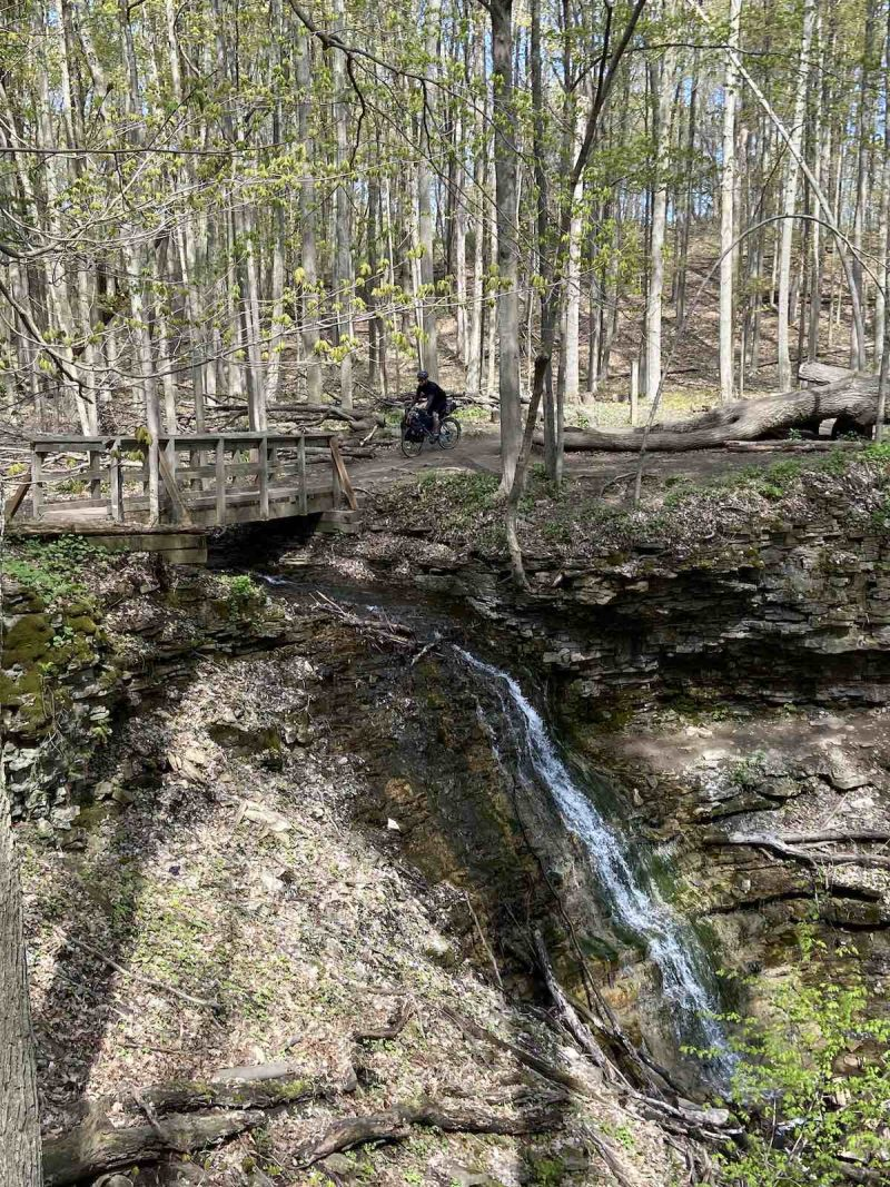 bikerumor pic of the day a cyclist is on a trail that edges the woods on one side and a rocky edge with a waterfall on the other a small bridge is before them, sunlight is coming through the trees and leaves are just beginning to open on the trees.