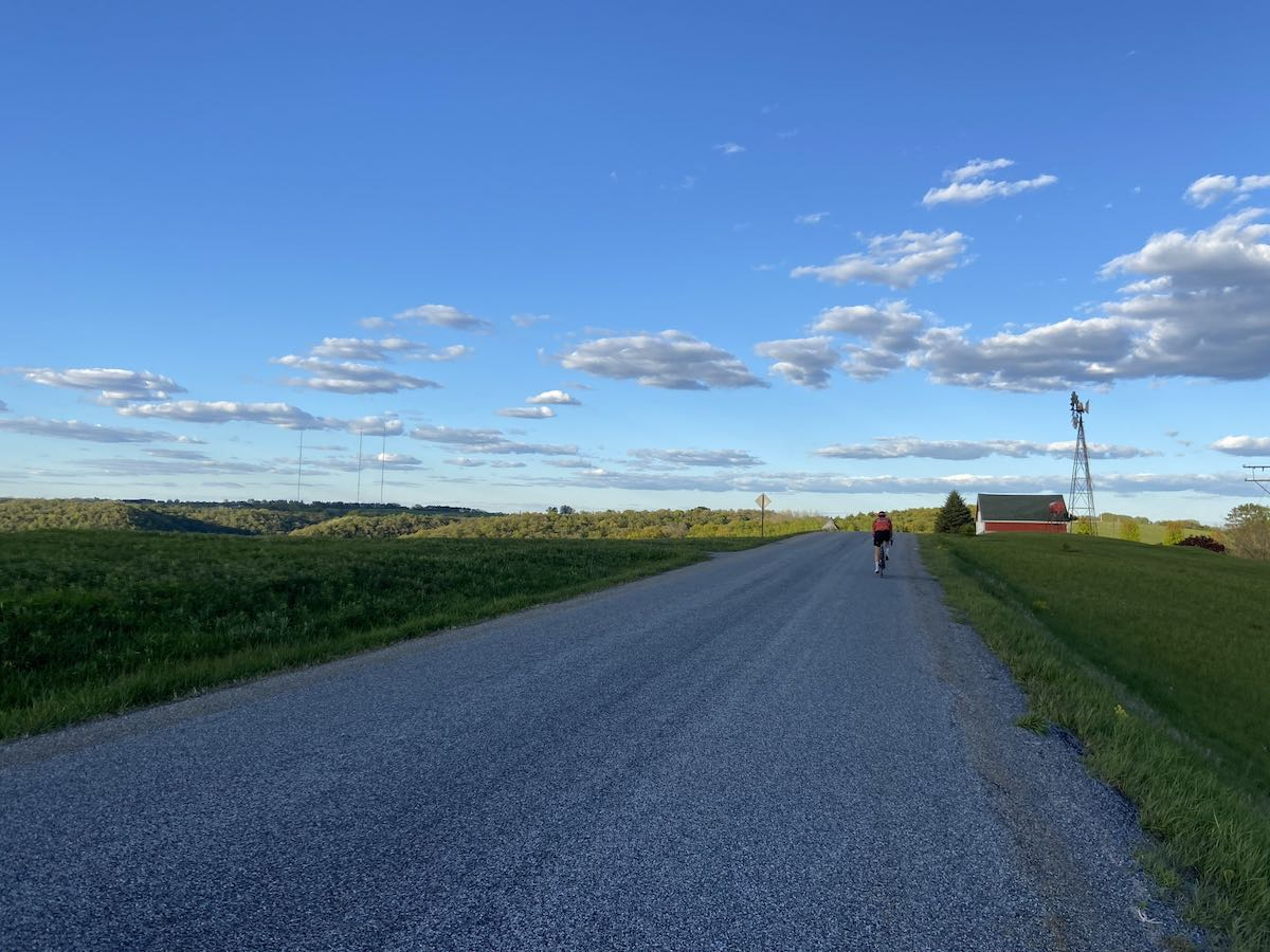 bikerumor pic of the day a cyclist is riding away from the camera on a road that is surrounded by green fields a small red barn and windmill can be seen just past the rider and there are tree-filled hills beyond that. the sky is blue and there are a few clouds in the sky at what looks like evening.