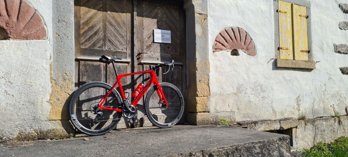 bikerumor pic of the day a red road bike leans agains the large wooden doors of an old mill. the building is of white stucco with stone accents and appears to be very old.