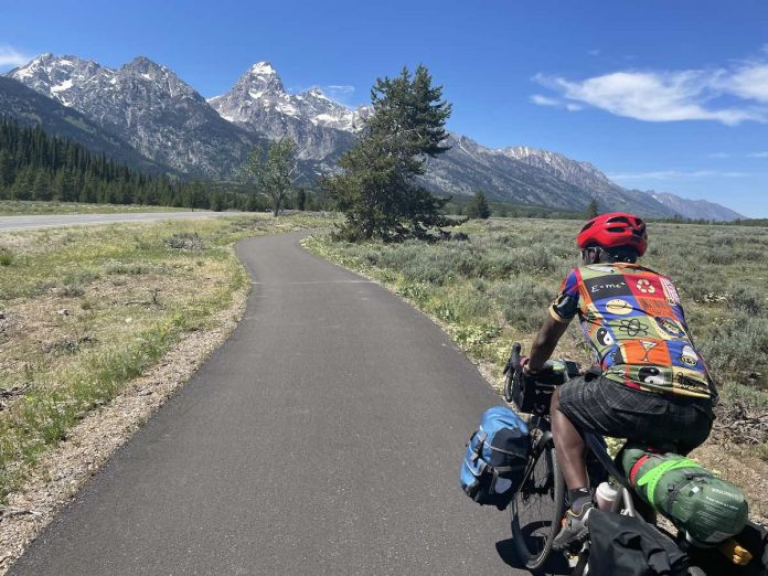 bikerumor pic of the day a cyclist rider a road surrounded by grassland leading towards a large pointed snow speckled mountain in the grand teton national park, wyoming.