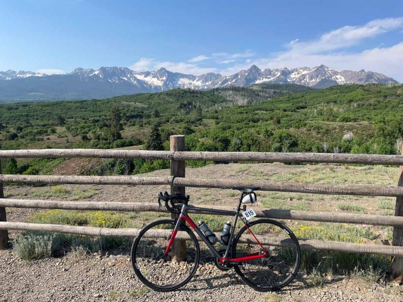 bikerumor pic of the day a bicycle leans against a wooden fence on a gravel road, a grassy field is next to it with tree covered hills and rocky mountains beyond, the sky is blue with a few clouds on the horizon.