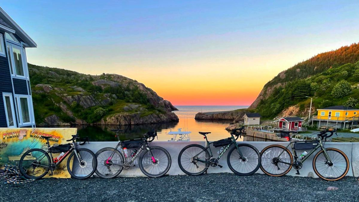 bikerumor pic of the day four bicycles lean against a concrete barrier on a gravel road, there is a small harbor in the background with small colorful buildings by the water, the sky is orange at the horizon and is reflecting on the water, the sky is clear.
