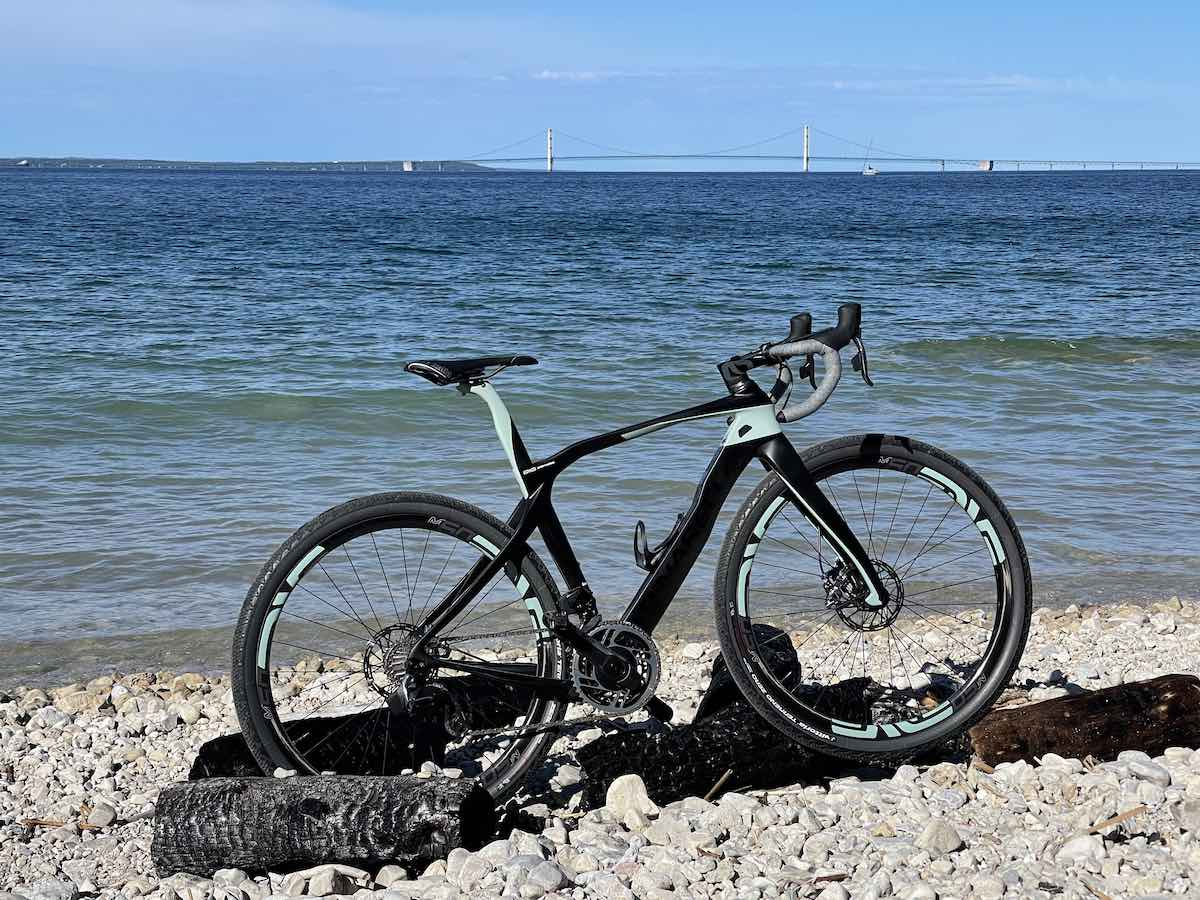 bikerumor pic of the day a bicycle lis on a beach with a long suspension bridge in the distance, the sky is clear and the sun is bright.