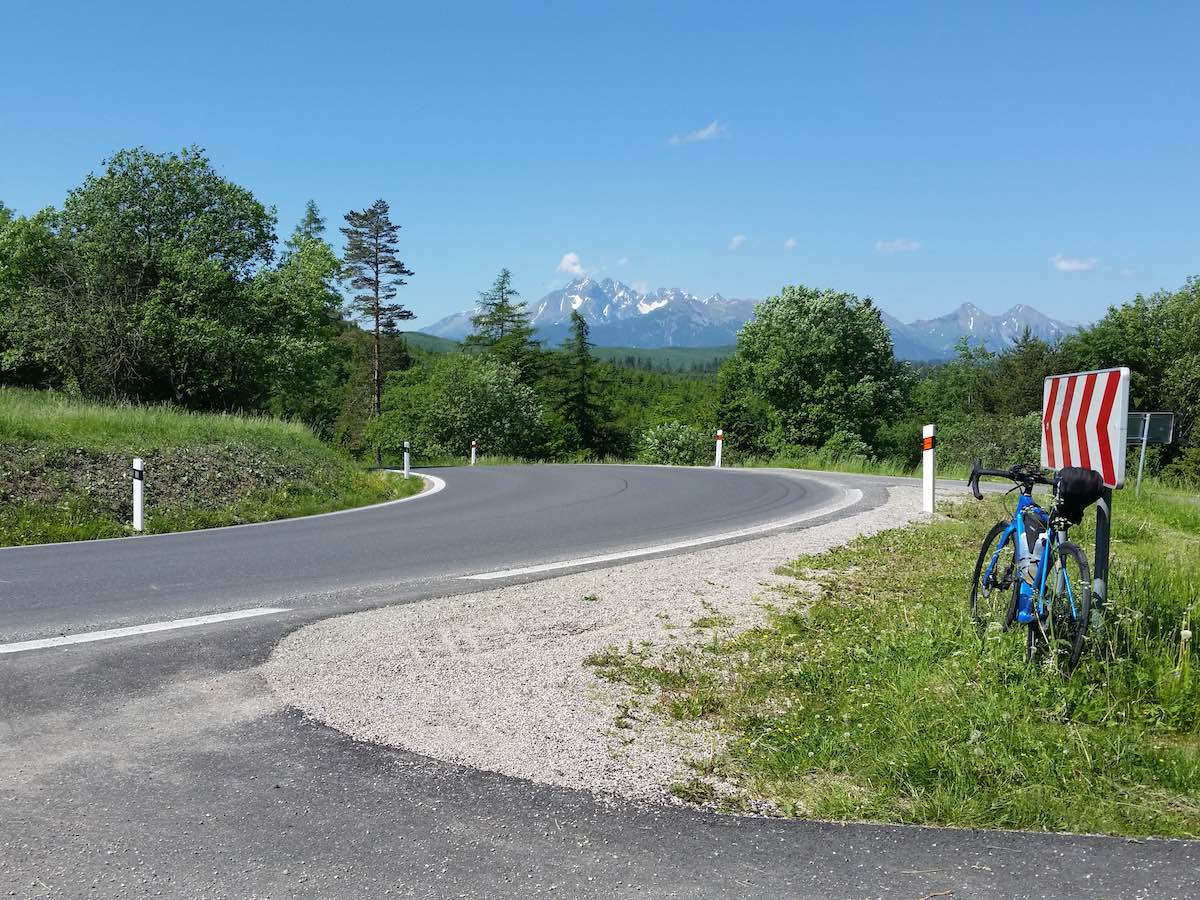 bikerumor pic of the day a road bike leans against a red and white road sign with a high mountain pass in the distance. The sky is clear and blue and there are tall trees along the road.