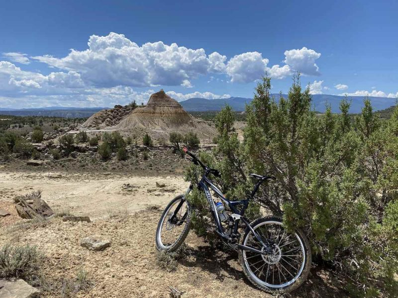 bikerumor pic of the day a bicycle leans against some scrubby bushes near a dirt trail, the sky is blue with fulffy white clouds in the distance and there are eroded rock formations in the background.