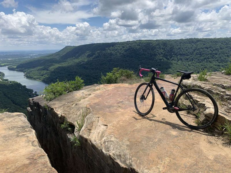 Bikerumor pic of the day a gravel bike is on a large rock slab looking out over green mountains, a river and valley below, the sky is blue and full of white fluffy clouds.