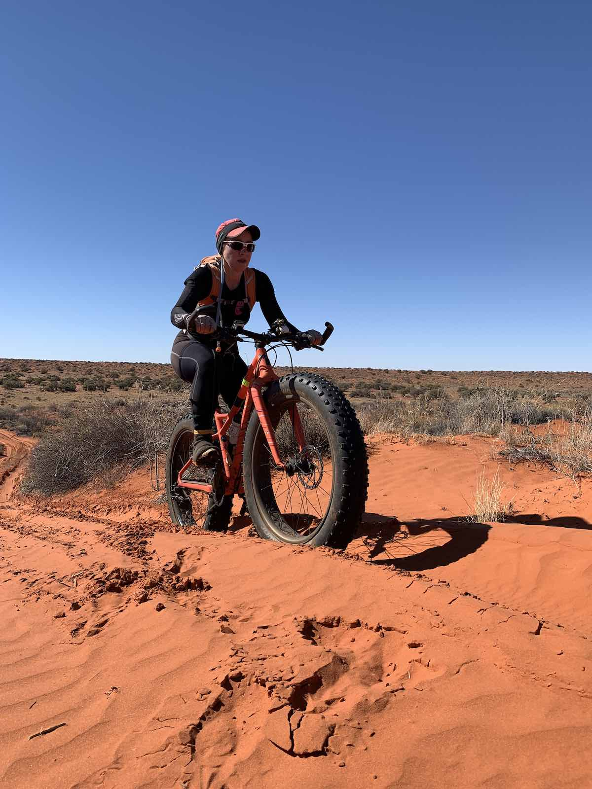 bikerumor pic of the day a cyclist rides a fat tire bicycle on red desert sand, the sky is clear and dark blue, there is brush growing in the flat distance.