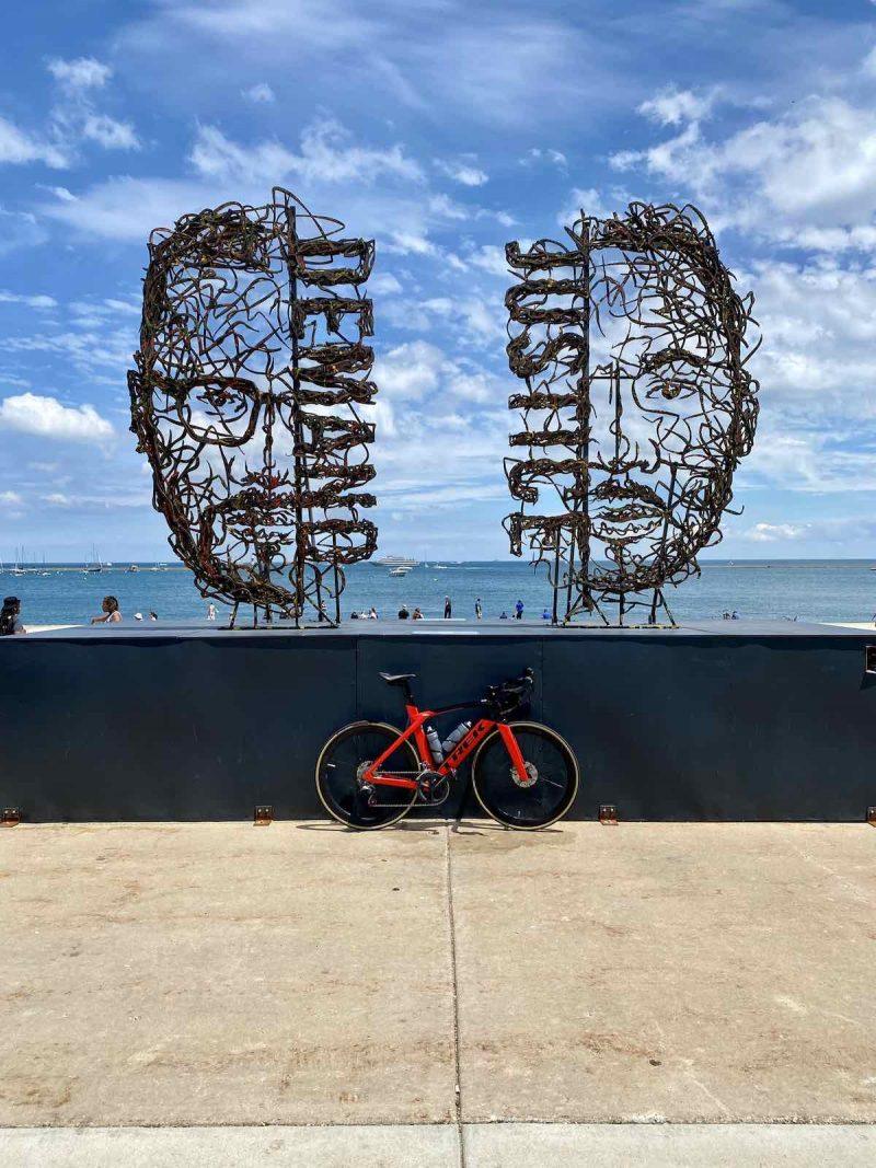 bikerumor pic of the day a red bicycle is leaning against a wall the borders a waterfront, there are two metal sculptures on the wall one is the face of malcom x with the word demand and the other is the face of martin luther king jr with the word justice on one side. the sky is blue with white fluffy clouds interspersed and there are people out by the water.