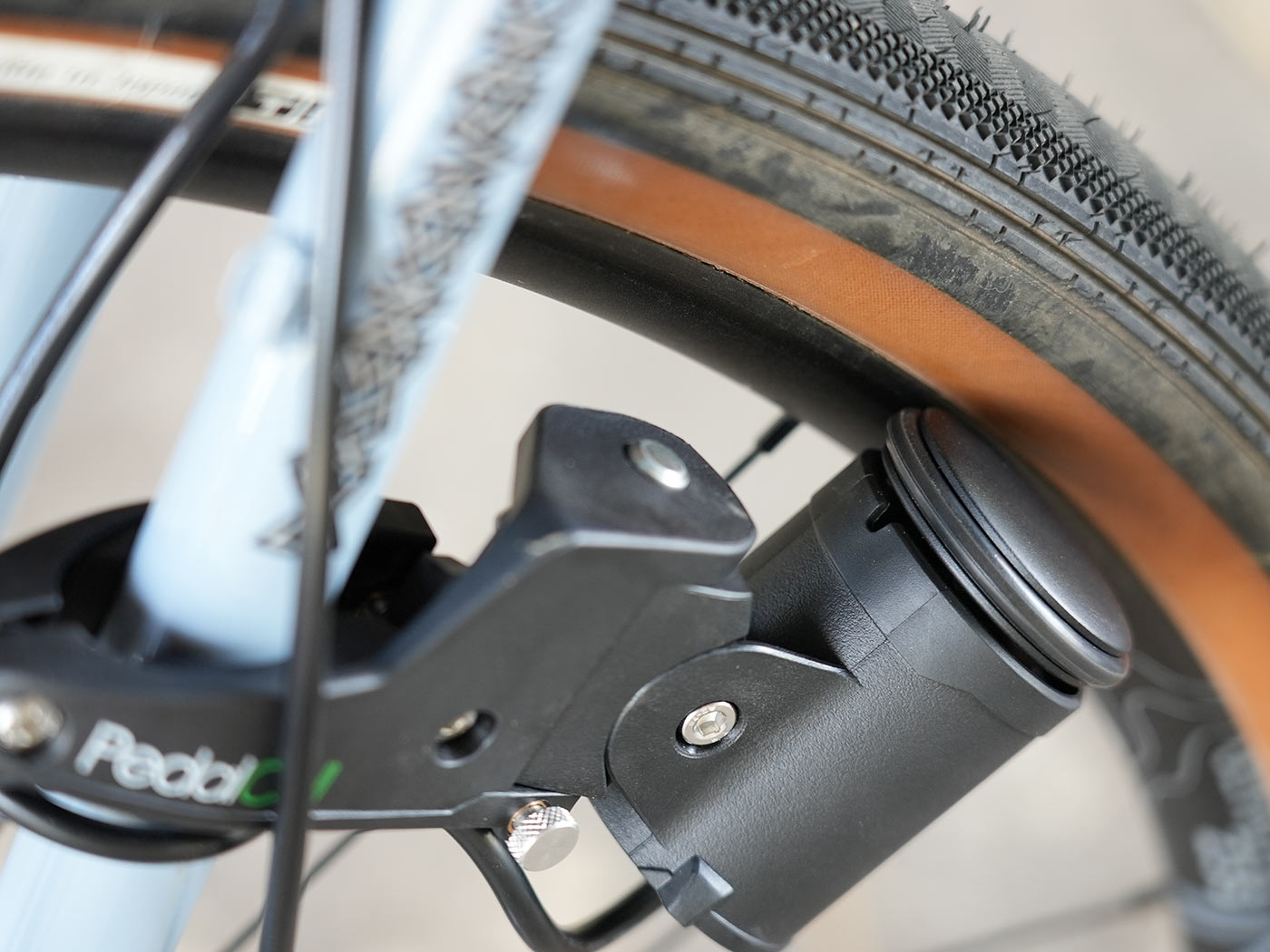 review of pedalcell rim dynamo shown closeup making contact with bicycle wheel rim