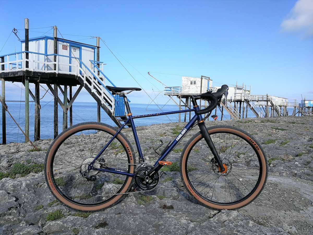 bikerumor pic o the day a bicycle is on a rocky beach in St Palais sur Mer there are freestanding structures on stilts at intervals along the shore the ocean is calm and there are no clouds in the sky.