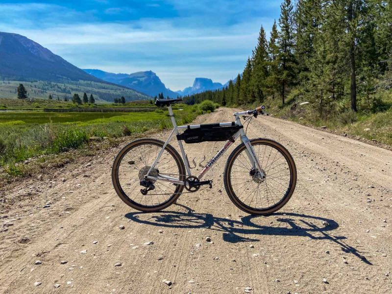 bikerumor pic of the day a gravel bike is displayed across a wide gravel and dirt road with a pine forest on the right and a green valley on the left with views of the tetons in the distance. the sky is bright and the sun is directly overhead.
