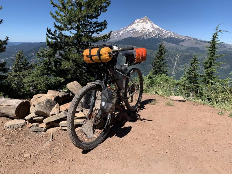 bikerumor pic of the day a bicycle with camping gear packed on it is on a clearing with pine trees surrounding it and a view of a snow capped mountain peak in the distance.