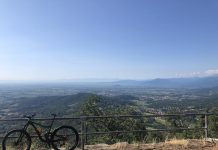 bikerumor pic of the day a bicycle leans against a metal railing overlooking a vast mountain region. the sky is clear with a slight haze over the horizon.