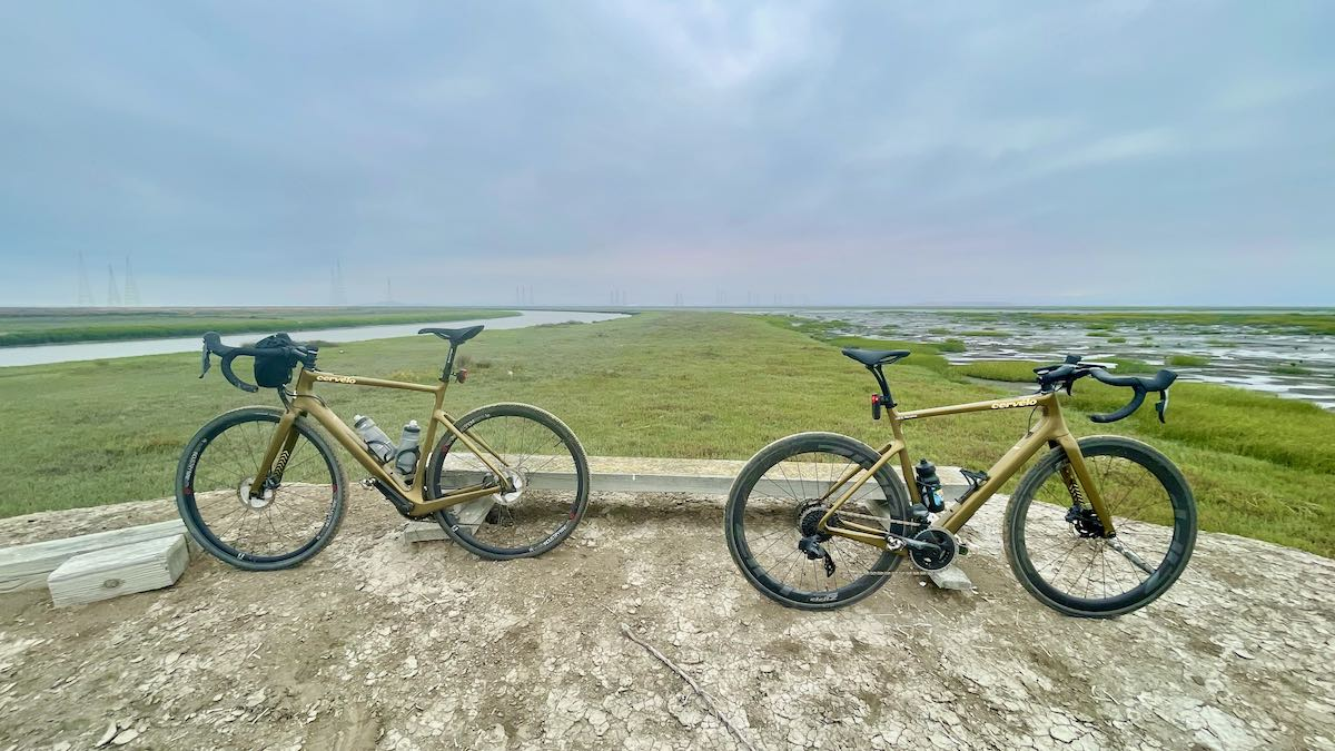 bikerumor pic of the day two gold cervelo bicycles posed in the baylands near alvero california, the land is flat with short grass and there is wetland surrounding, the sky is overcast with a slight hint of sunset in the distance.
