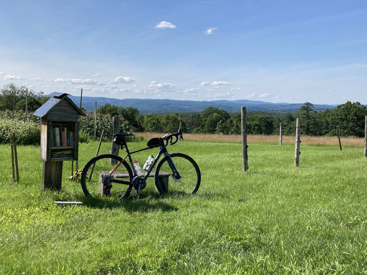 bikerumor pic of the day a bicycle is in the middle of a grassy field with a view over the surrounding low mountains, the bike leans against a wire fence and there is a small cabinet with clear glass doors containing books next to it. the sun is high and there are small white clouds in the distance.