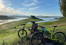 bikerumor pic of the day two mountain bikes lean against a stump in a gently sloping grassy field, there is a lake in the distance and there are whips clouds in the blue sky.