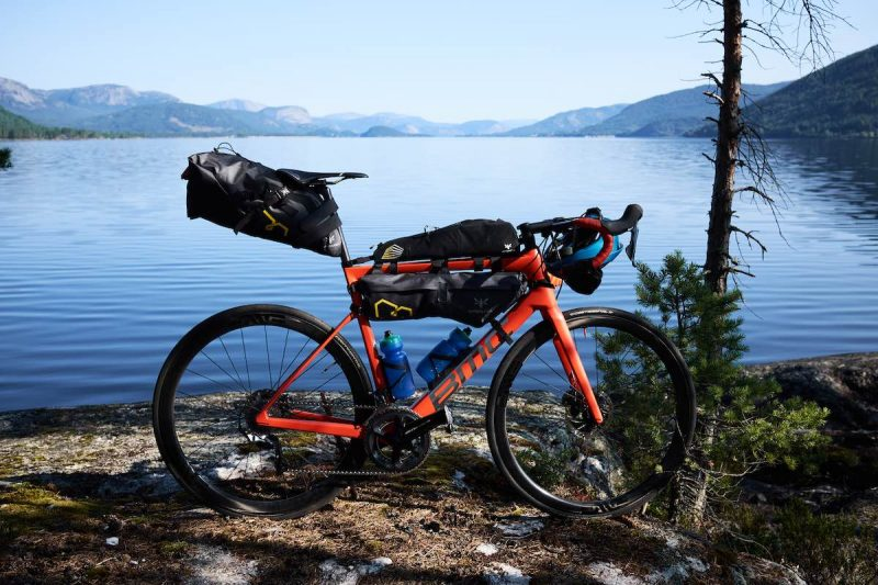 bikerumor pic of the day a bicycle has bike packing bags on it and is posed in front of a large calm lake with mountains surrounding it.
