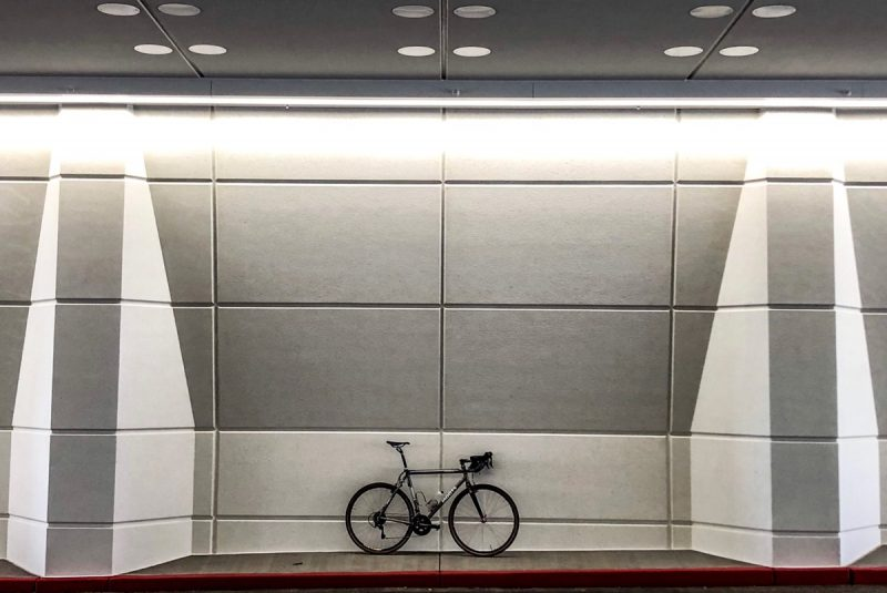 Bikerumor pic of the day a bicycle is leaning against the inside of a tunnel, the panels inside the tunnel are very geometric and the lights are such that it looks very three dimensional and grey.