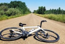 bikerumor pic of the day a bicycle is laid on a gravel road the perspective is low and makes the road look like it goes straight forever and disappears, there is green grass and scrub brush neither side of the road and the sky is clear.