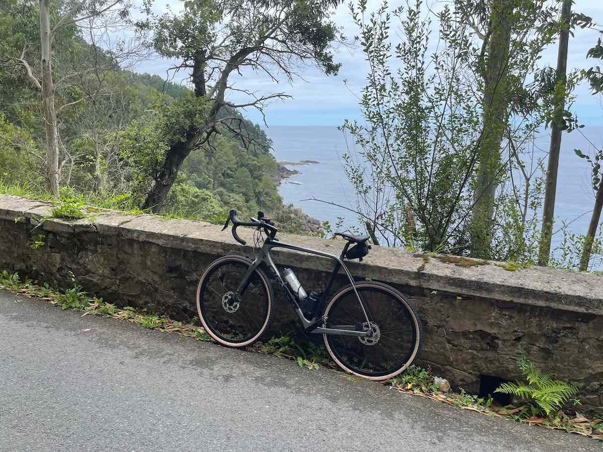 a bicycle leans against a low stone wall beside a road, beyond is the steep side of a mountain and the ocean.