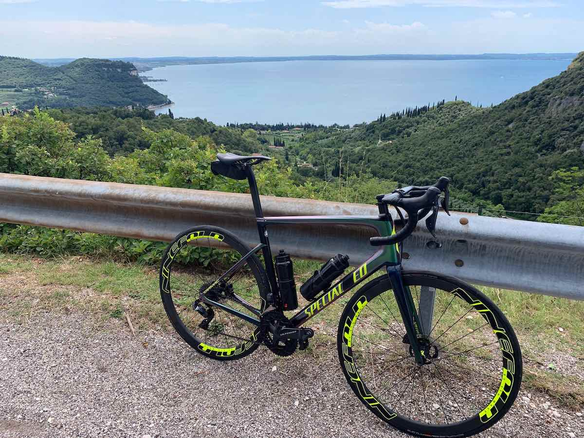 bikerumor pic of the day a road bike is leaning against a metal auto barrier on a road overlooking a large lake, there are a lot of green trees around the lake, the sky is blue with clouds on the horizon.