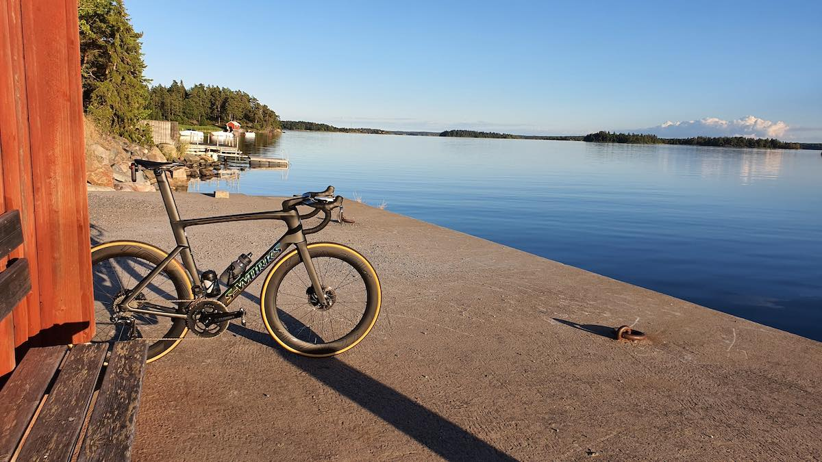 bikerumor pic of the day a specialized road bike leans against a small outbuilding on the edge of a pier looking out over smooth water, the sky is clear and reflecting off the water.
