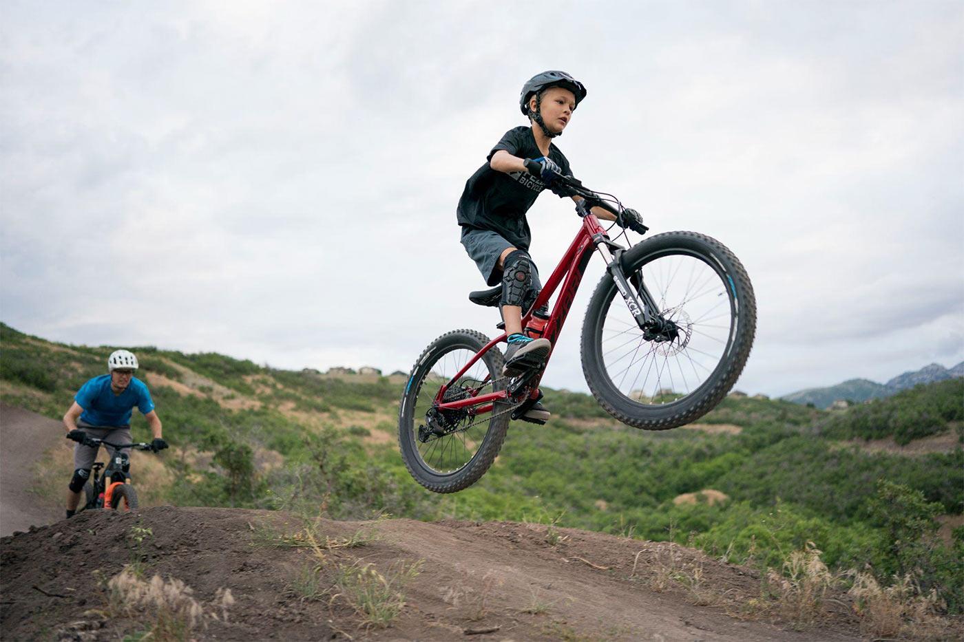 boy jumping a ramp on fezzari lone peak kids mountain bike