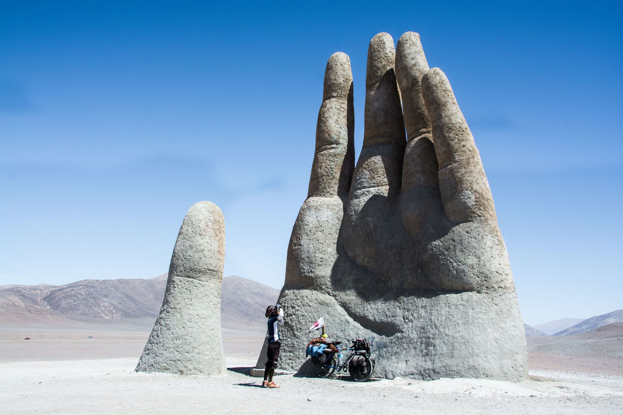 50 ways to cycle the world bike touring sculpture hand