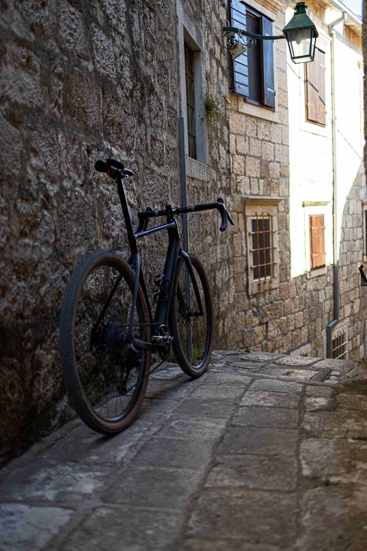 bikerumor pic of the day a road bike leans against a stone building in a narrow stone paved alley in croatia.