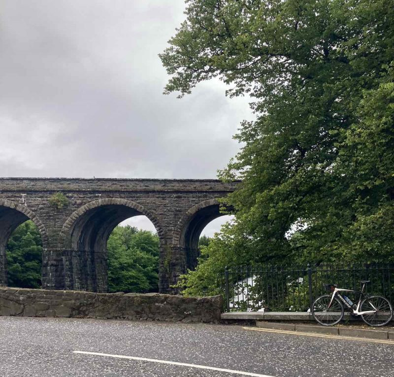 bikerumor pic of the day a road bike leans against a low stone wall the borders the road with a stone arched bridge in the distance. the sky is cloudy and bright.