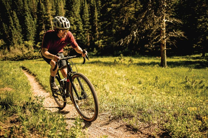 sram xplr gravel bike group overview with cyclist riding through the forest