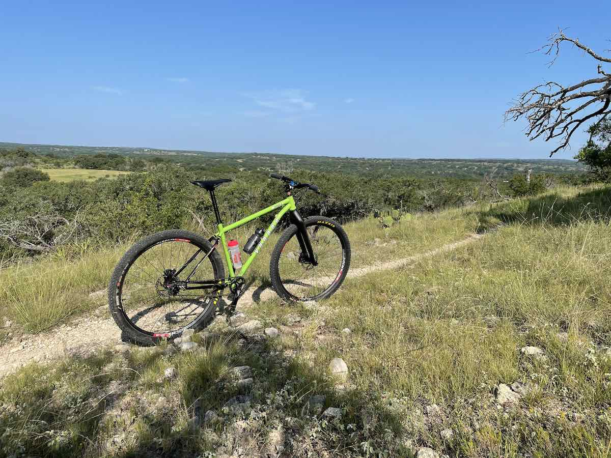 bikerumor pic of the day a mountain bike is on a narrow dirt trail on a ridge overlooking a vast flat expanse of land the sky is clear and the sun is high