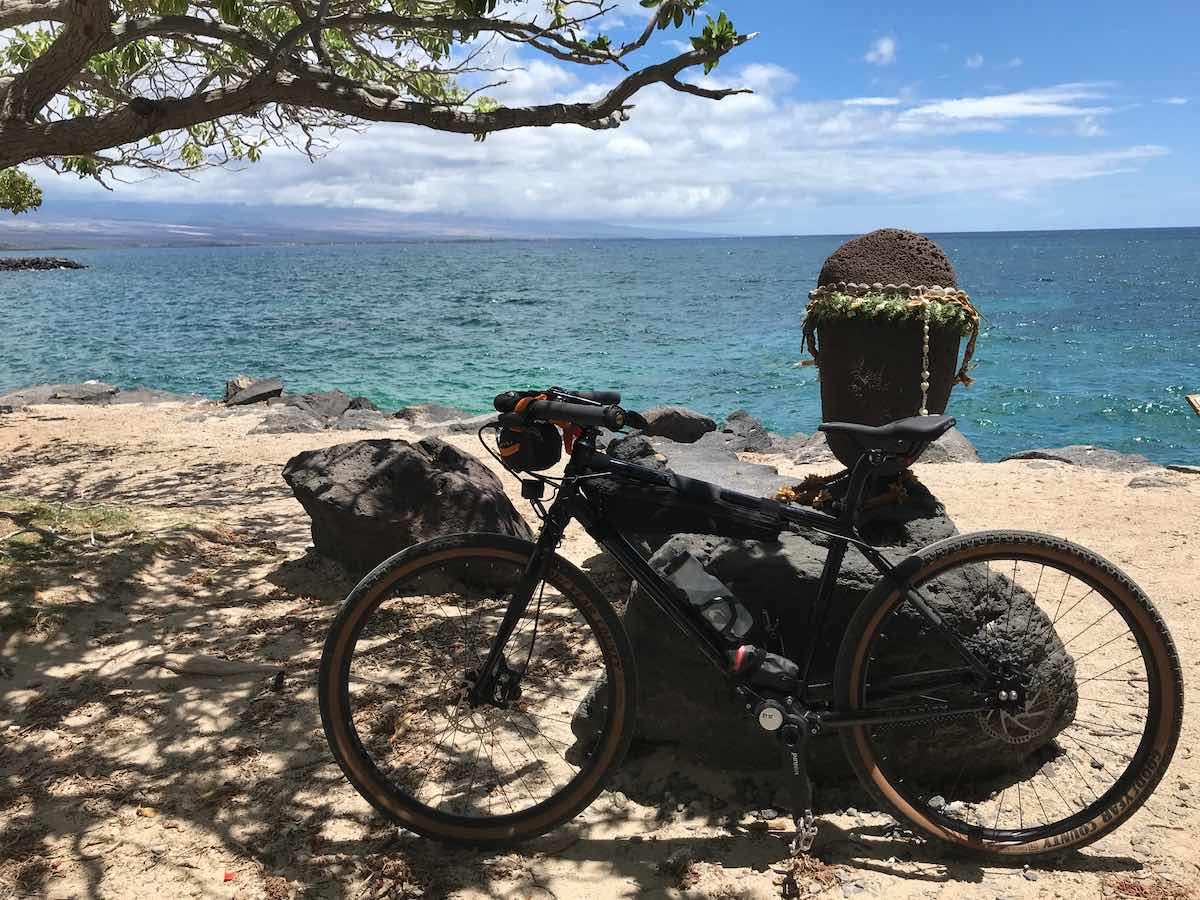 bikerumor pic of the day a bicycle leans against volcanic rock on white sandy beach and blue green ocean waters.