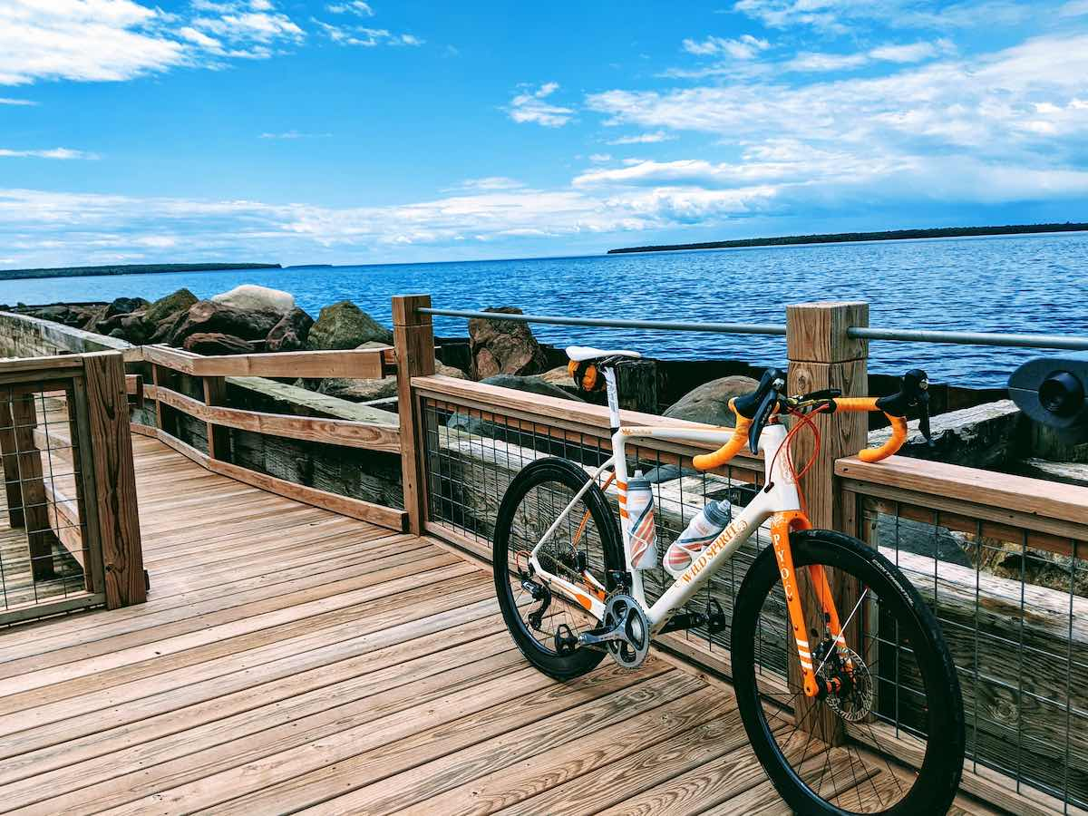 bikerumor pic of the day sand point wisconsin a bicycle leans against the wooden fence of a dock leading out over lake superior with small islands in the distance and partial clouds in the blue sky